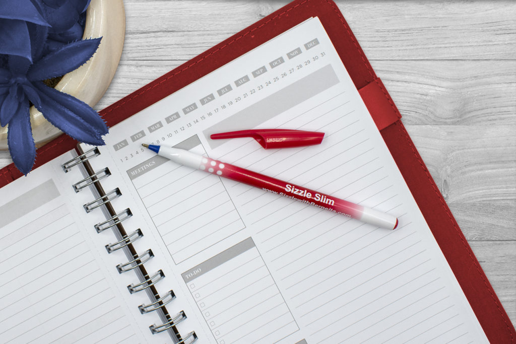 A red MaxGlide Stick promotional pen on a planner