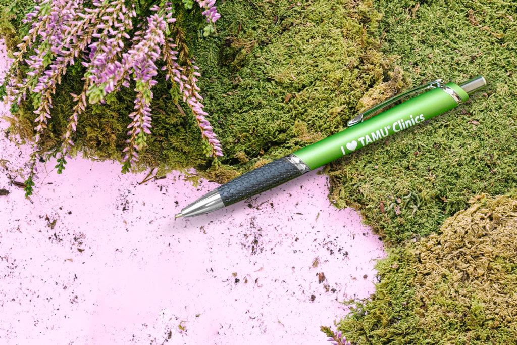 XeeDee green promotional pen on green moss