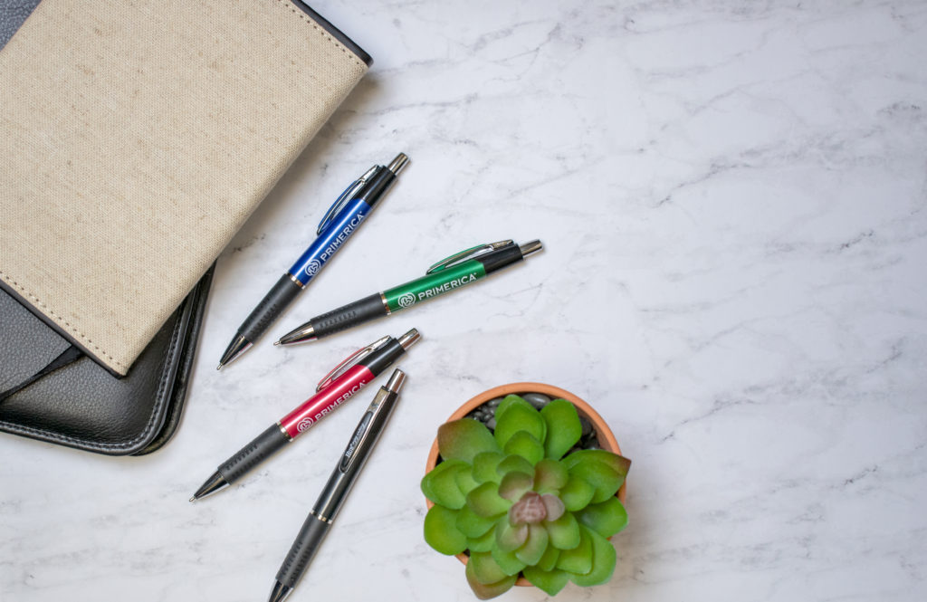 Consuelo promotional pens on a marble counter with journals