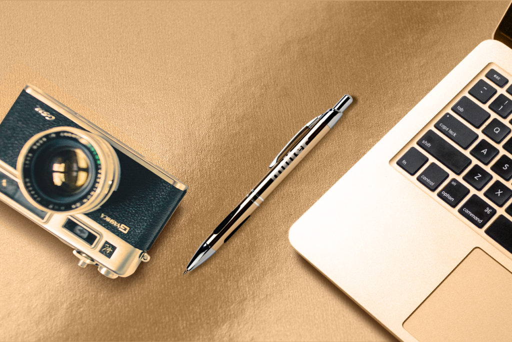 Vienna mechanical pencil in gold on a table with a camera and laptop