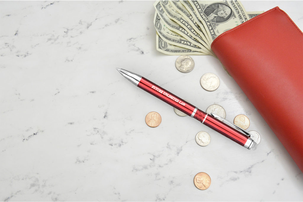 Farella Stylus pen in red on a marble counter with money